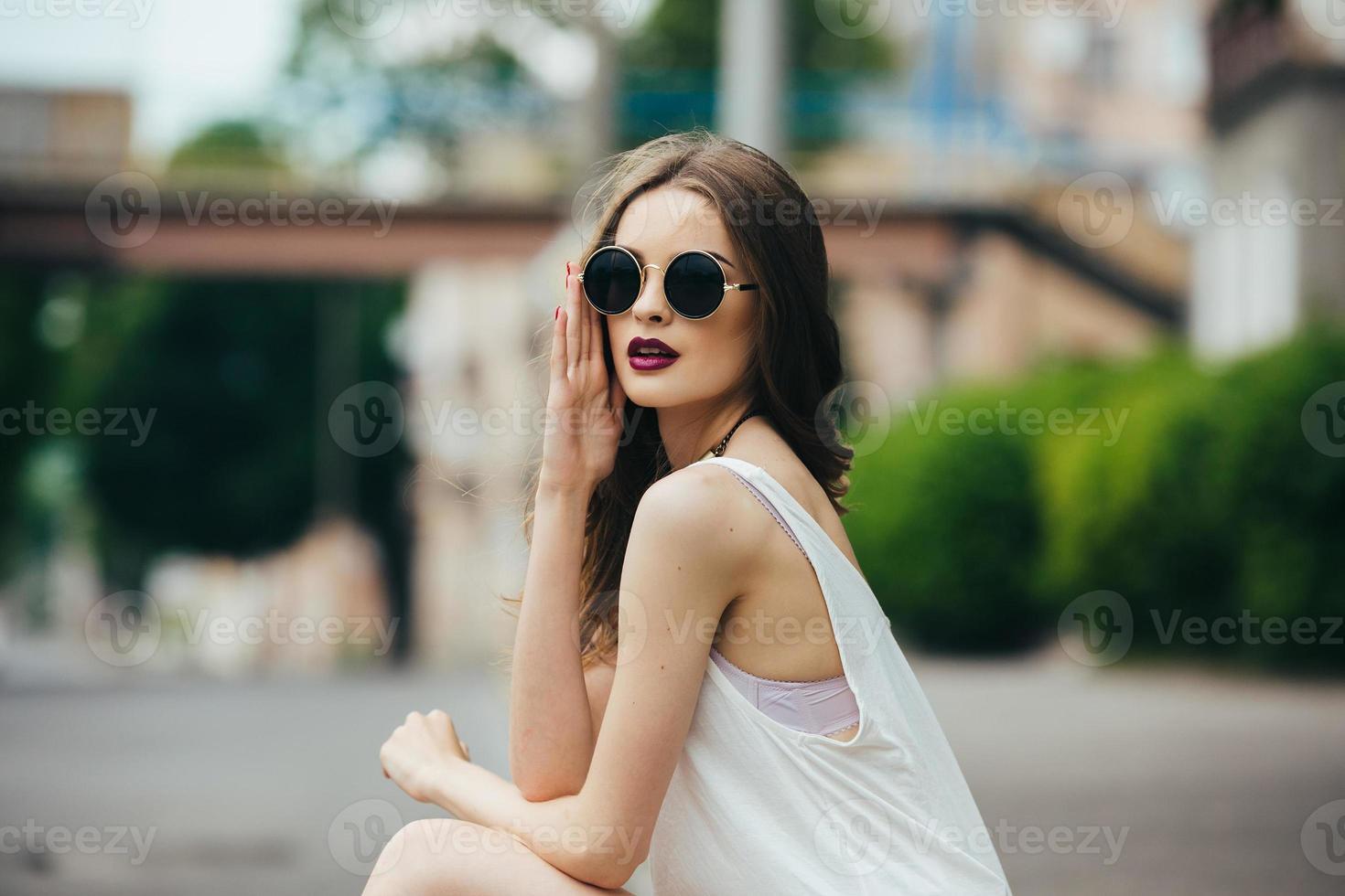 beautiful girl in sunglasses sitting photo