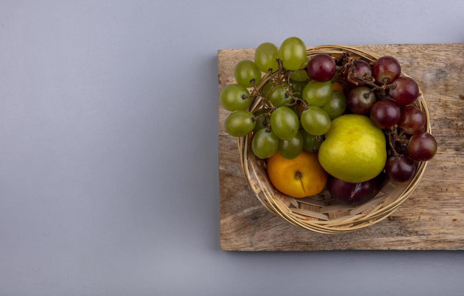 Surtido de frutas en una canasta sobre fondo neutro foto