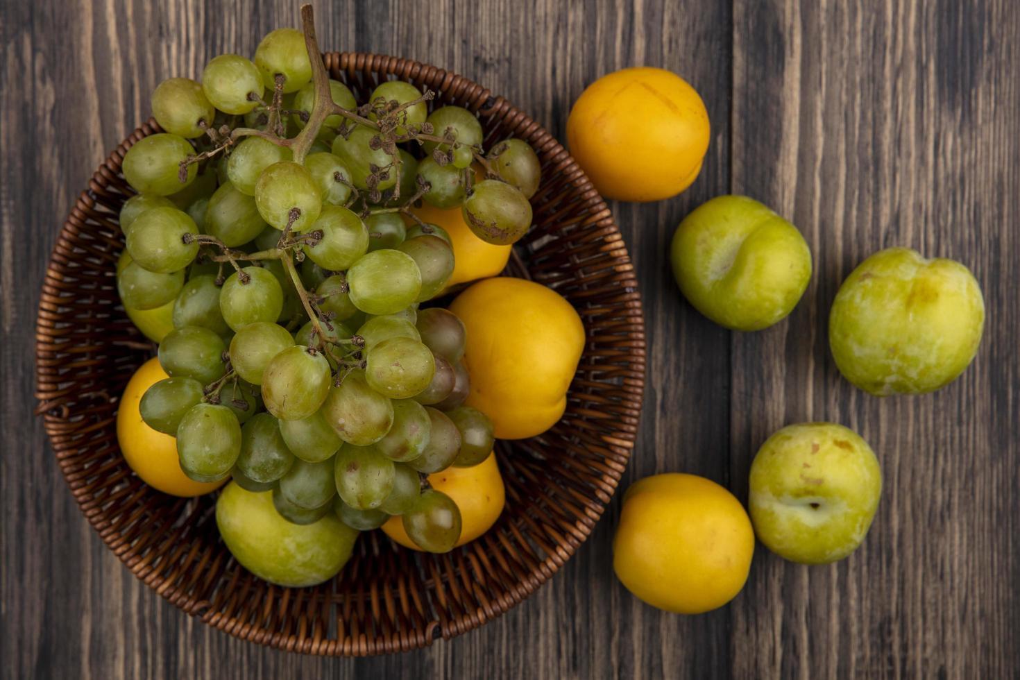 Surtido de frutas en una canasta sobre fondo de madera foto