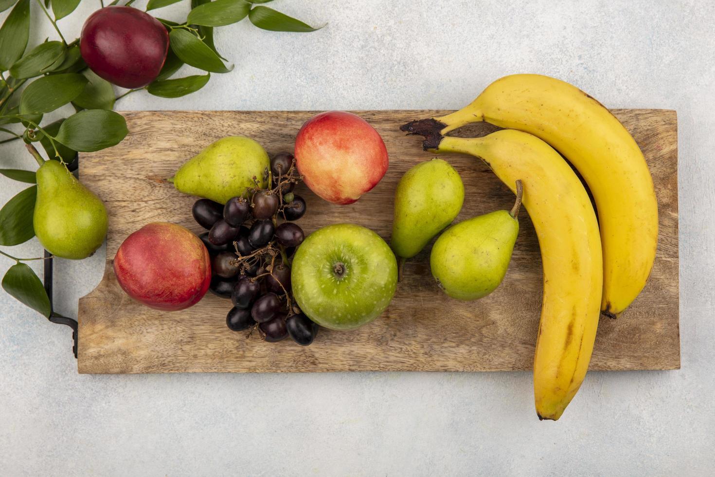 Surtido de frutas sobre tabla de cortar y fondo neutro foto
