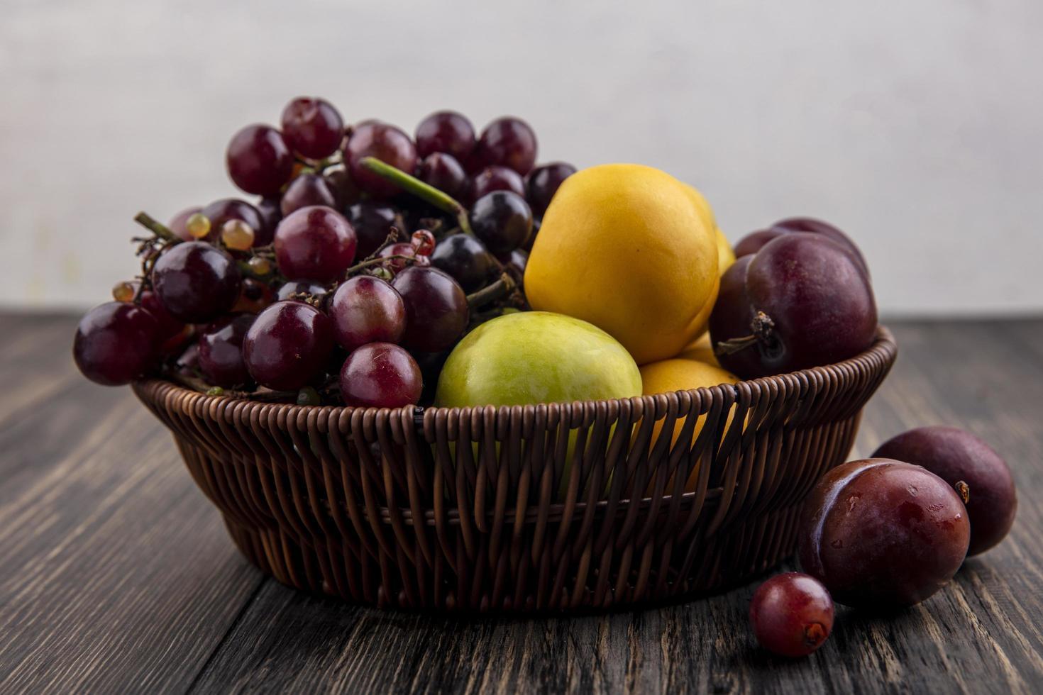 Surtido de frutas en una canasta sobre superficie de madera foto