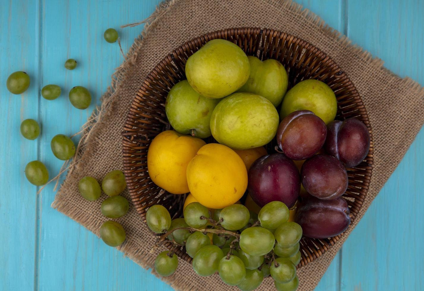 Surtido de frutas en una canasta sobre fondo azul. foto