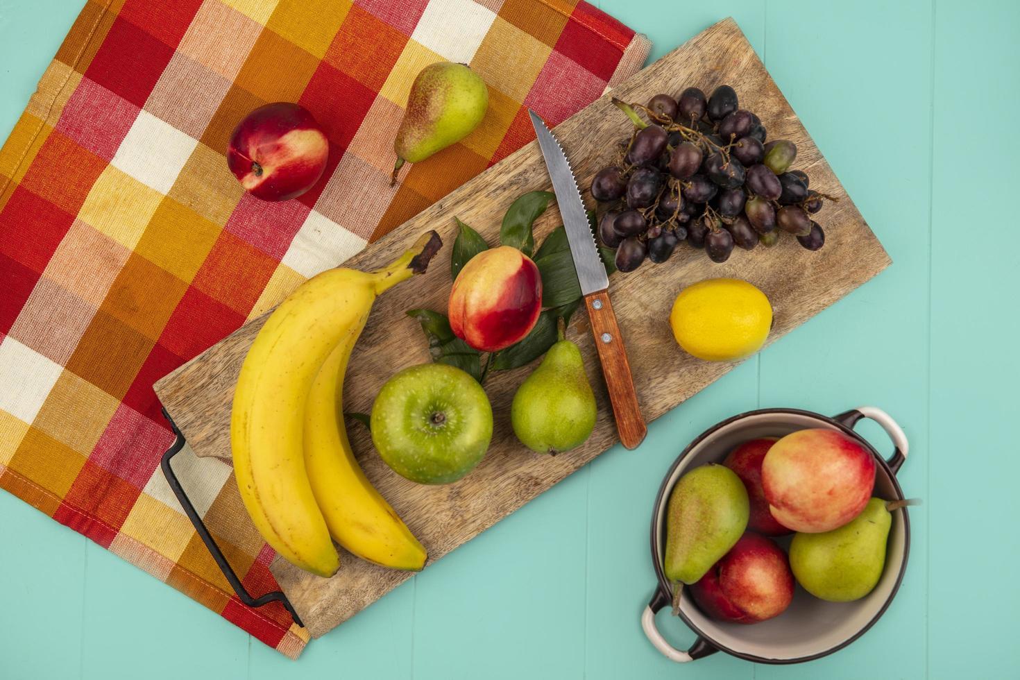 Surtido de frutas en la tabla de cortar con tela de otoño sobre fondo azul. foto