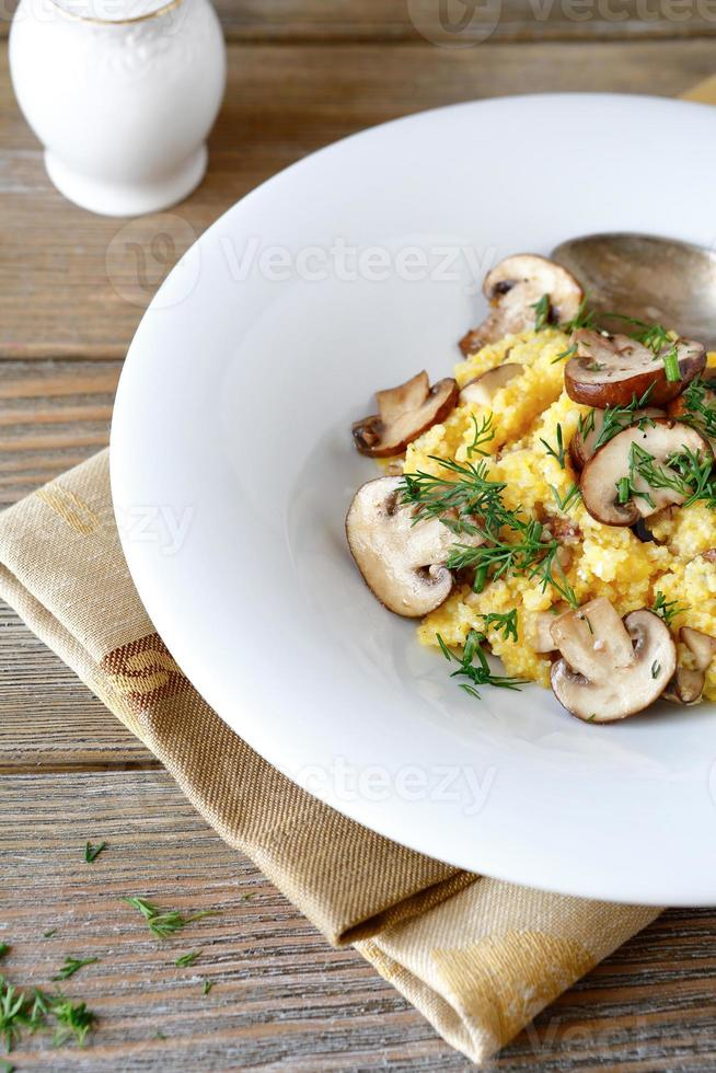Polenta with mushrooms and greens in the white plate photo