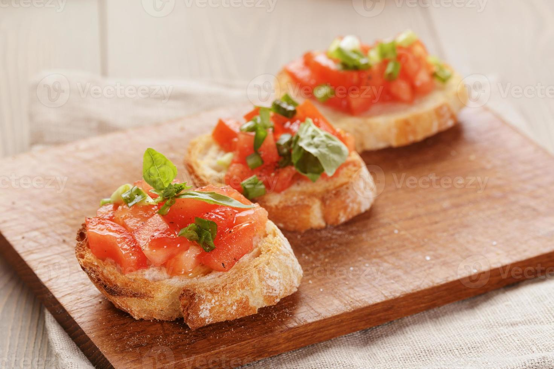 simple italian appetizing bruschetta with tomato and basil, on o photo