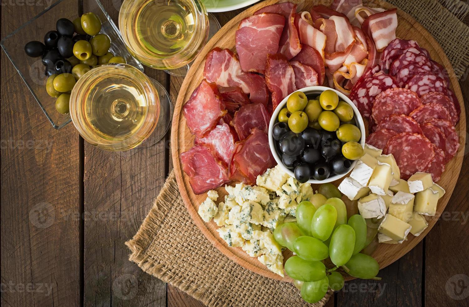 Antipasto catering platter with bacon, jerky, salami, cheese and grapes photo