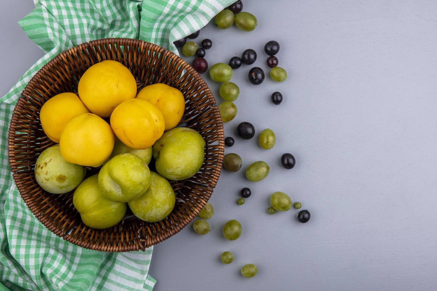 Surtido de frutas en una canasta sobre tela escocesa con espacio de copia foto