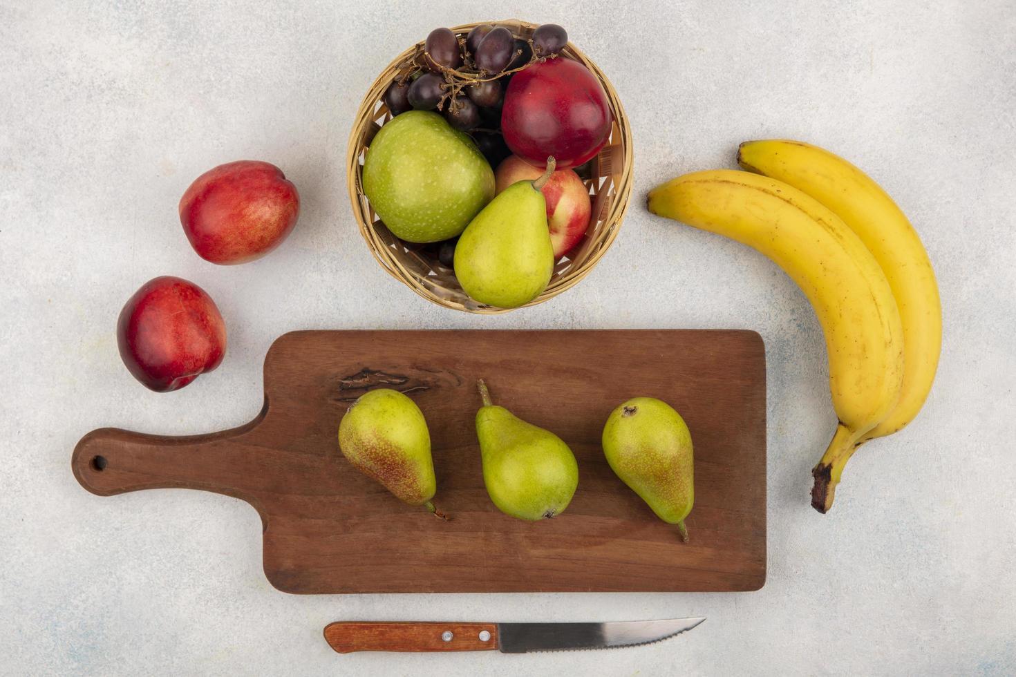 Surtido de frutas en la tabla de cortar sobre fondo neutro foto