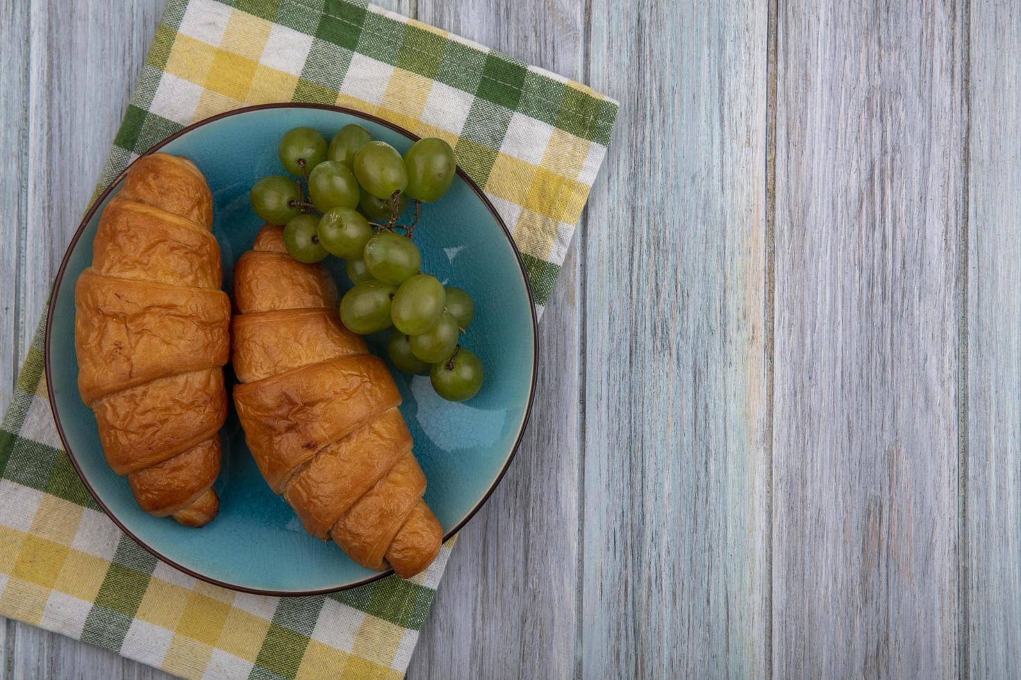 croissants y uvas en tela escocesa y fondo de madera foto