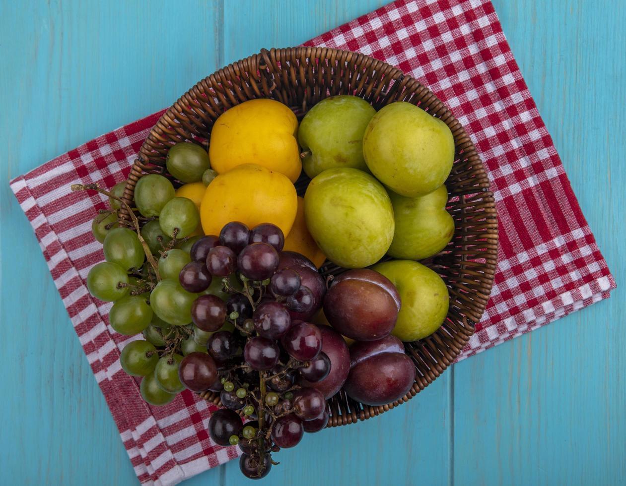 Surtido de frutas sobre tela escocesa y fondo azul. foto