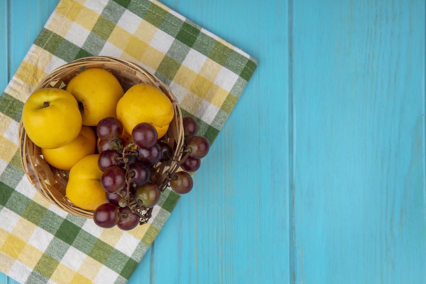 Fruta en una canasta sobre tela escocesa sobre fondo azul con espacio de copia foto