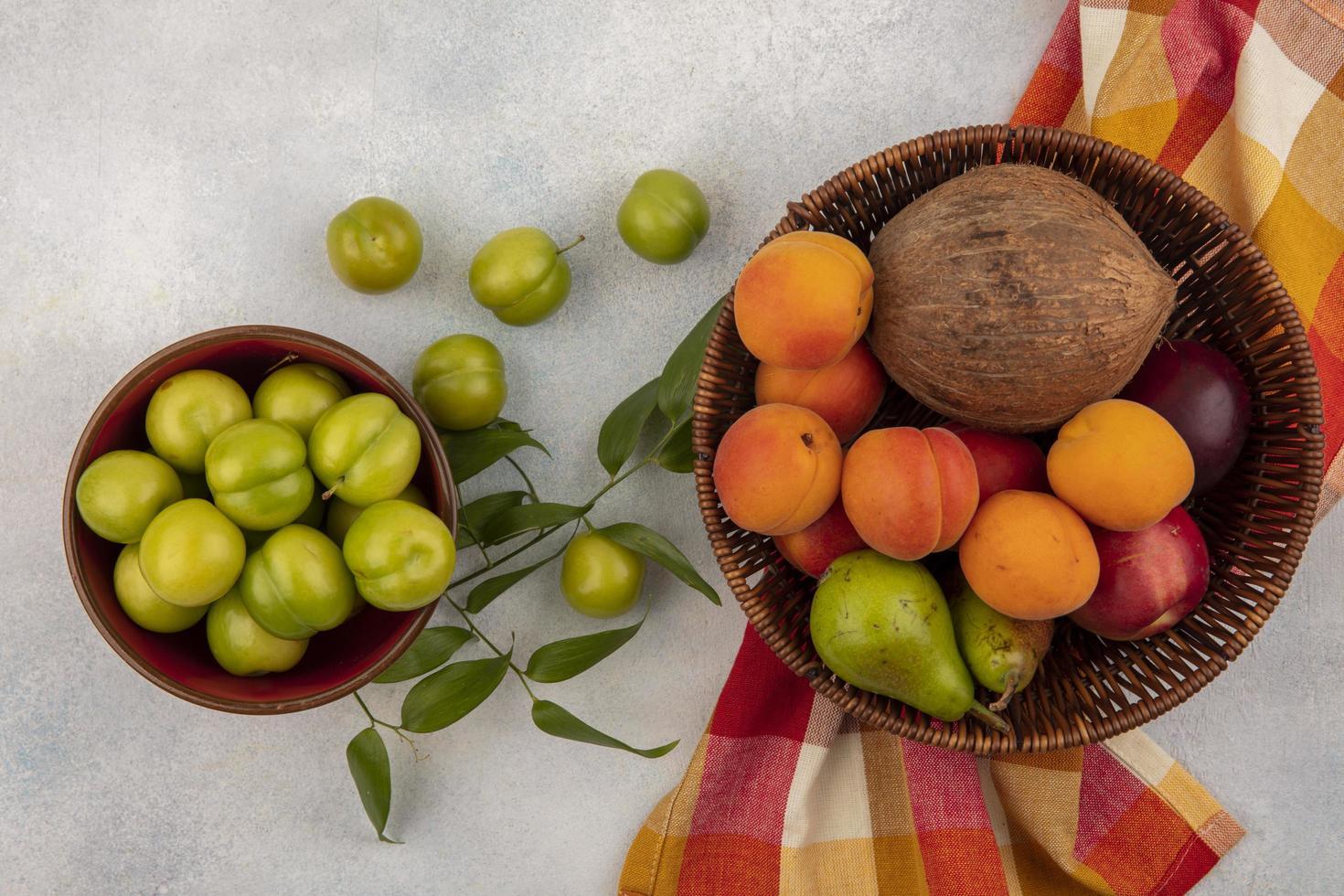 Surtido de frutas en una canasta y un tazón. foto