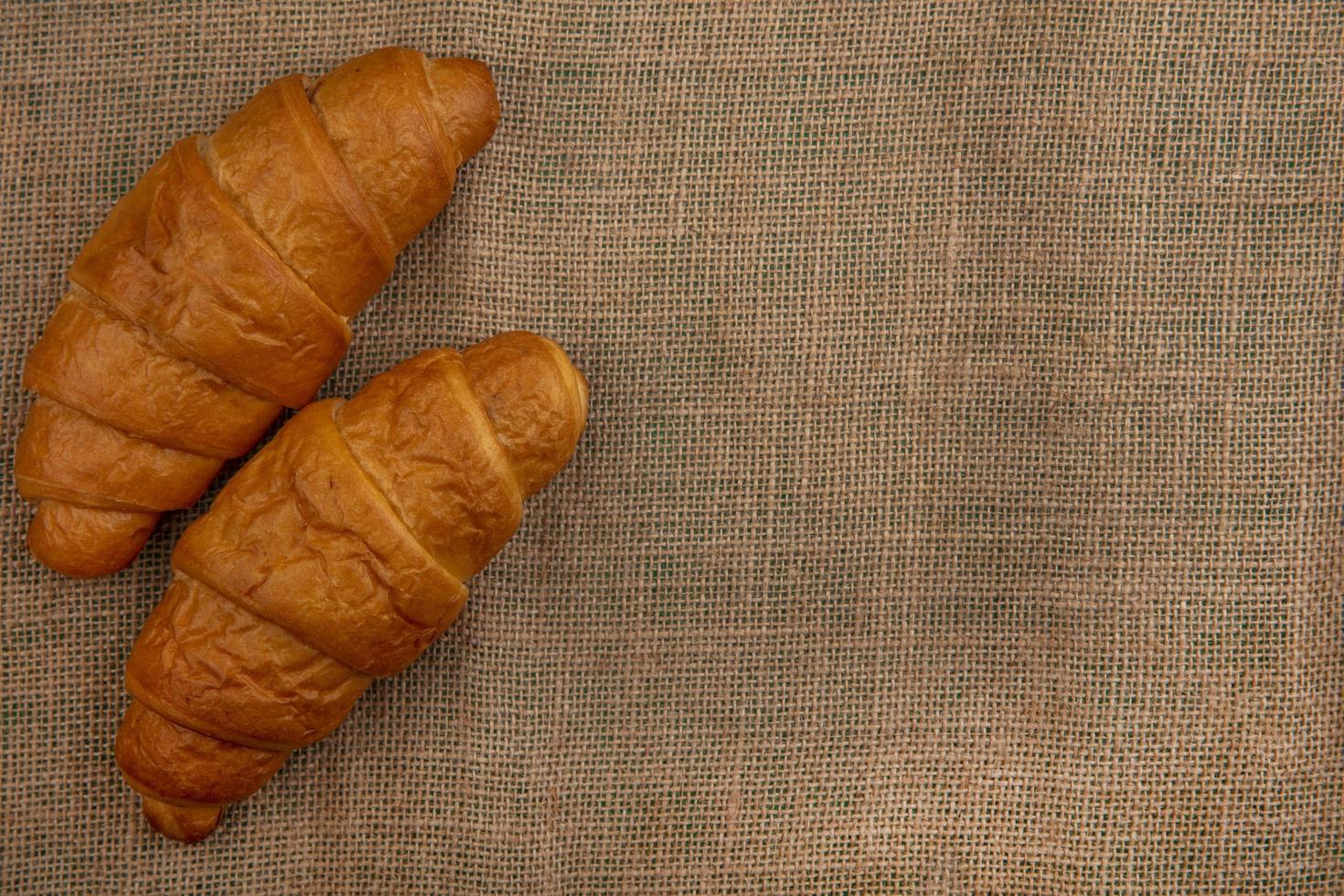 Croissants sobre fondo de tela de saco con espacio de copia foto