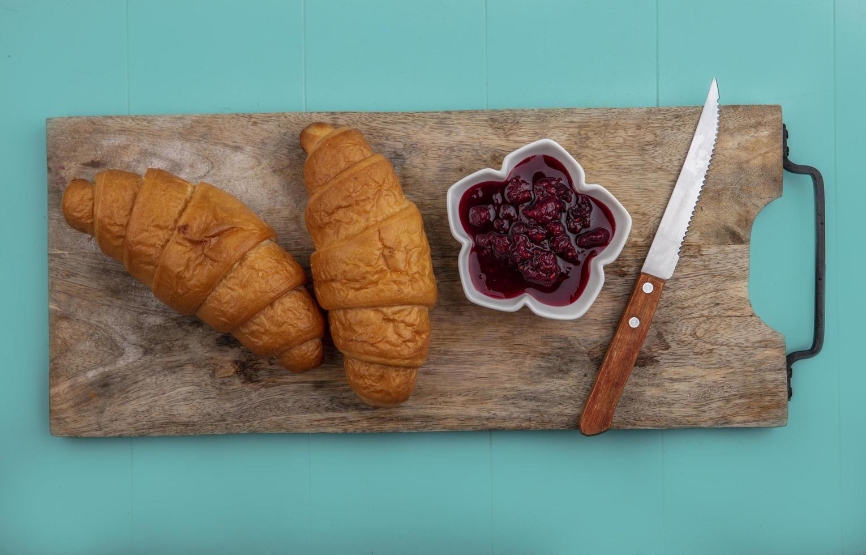 Croissants y mermelada de frambuesa con un cuchillo sobre la tabla de cortar sobre fondo azul. foto