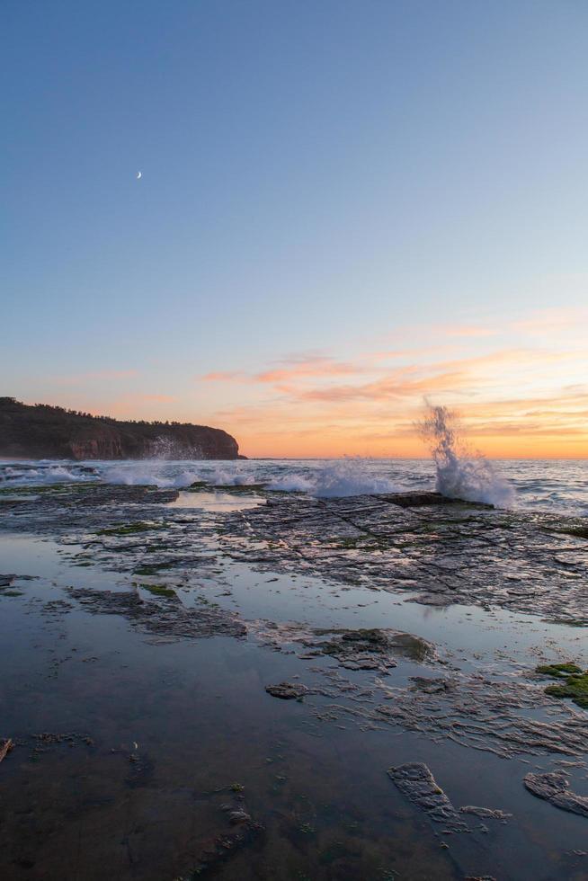 olas chapoteando en la orilla al atardecer foto