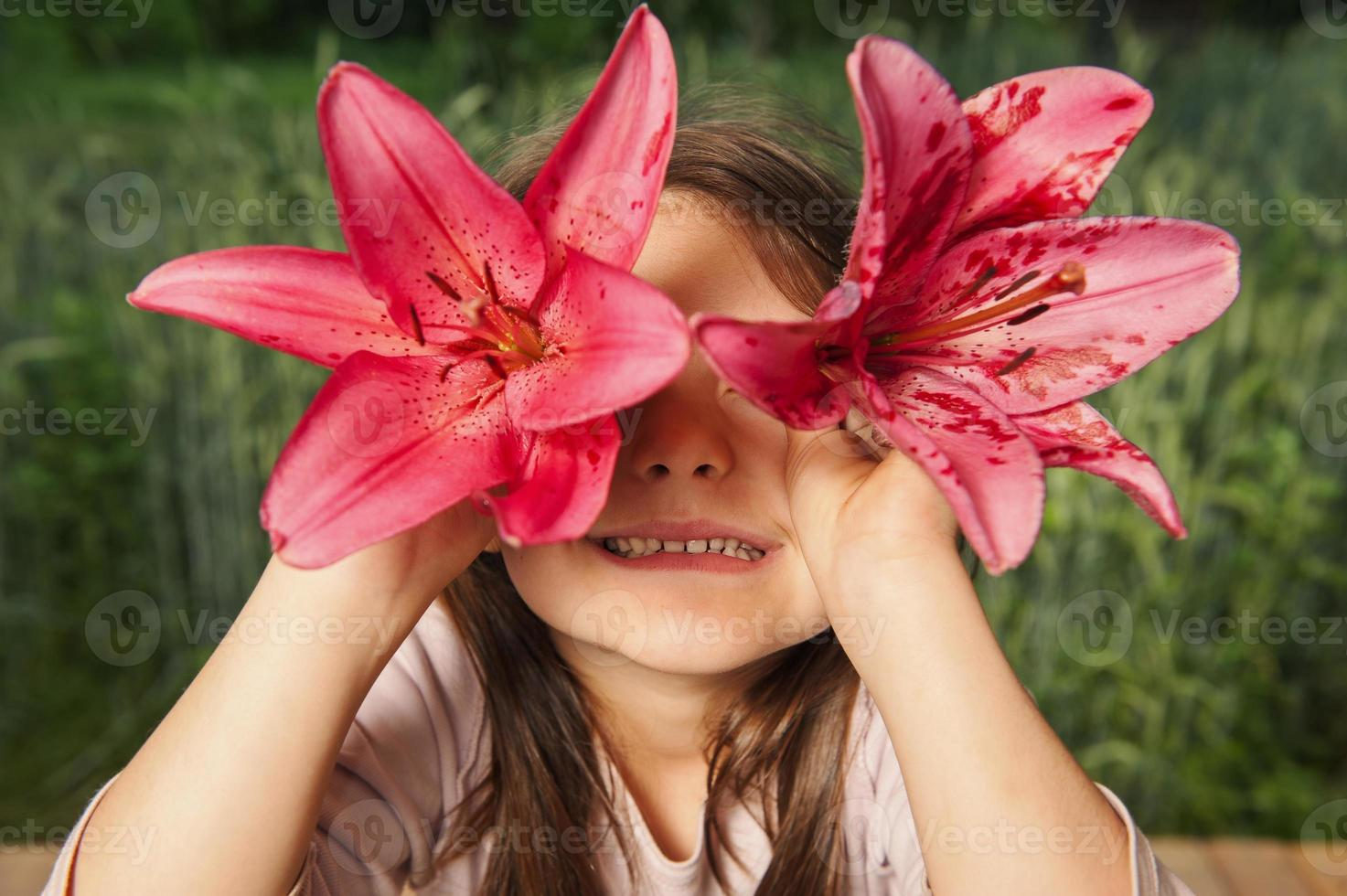 Cheerful girl playing with flowers, looking into  camera through  lily photo