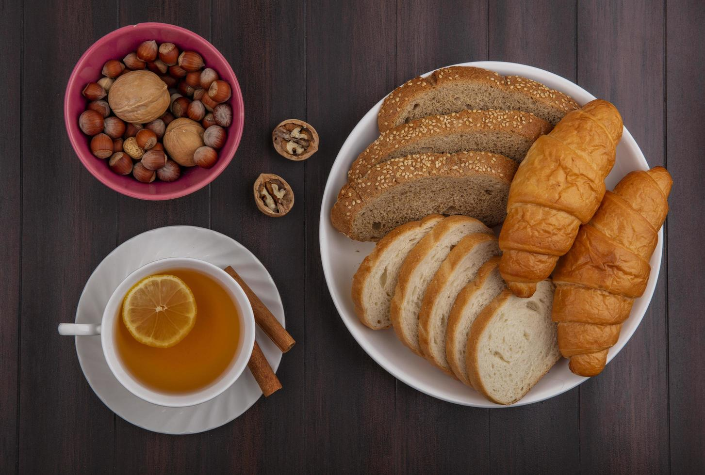 Sliced bread with nuts and tea on wooden background photo