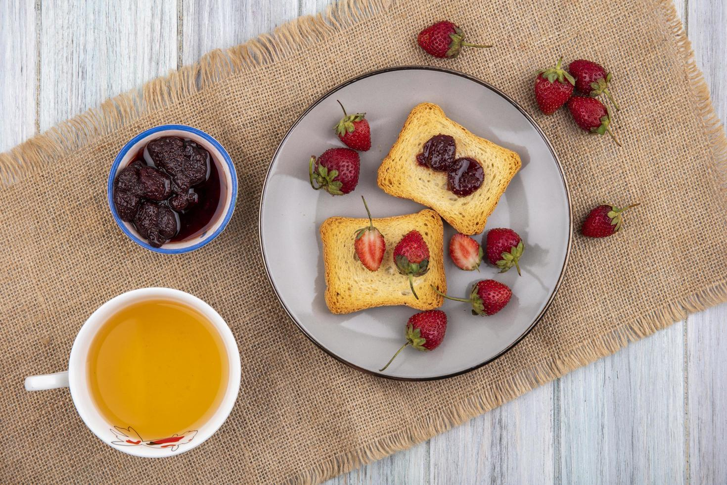 Tostadas y fruta en un plato sobre fondo de madera gris foto