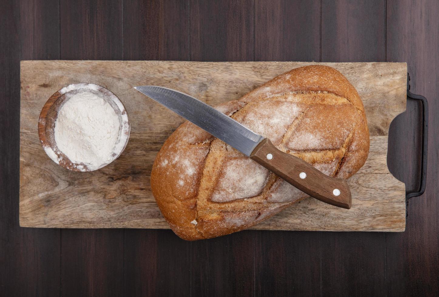 Pan fresco en la tabla de cortar sobre fondo de madera foto