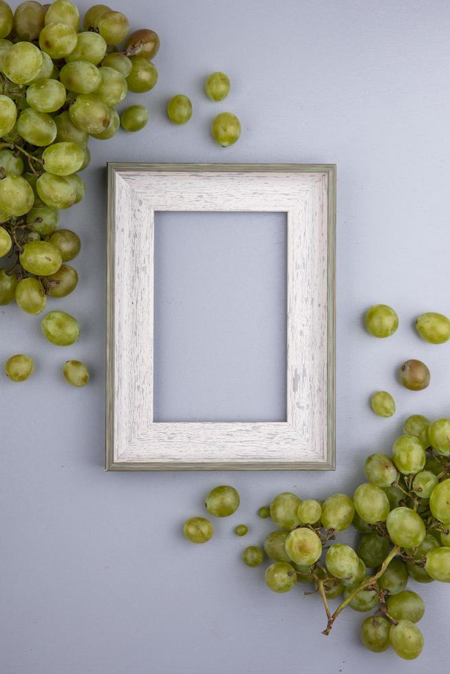 Fresh grapes surround a frame on gray background with copy space photo