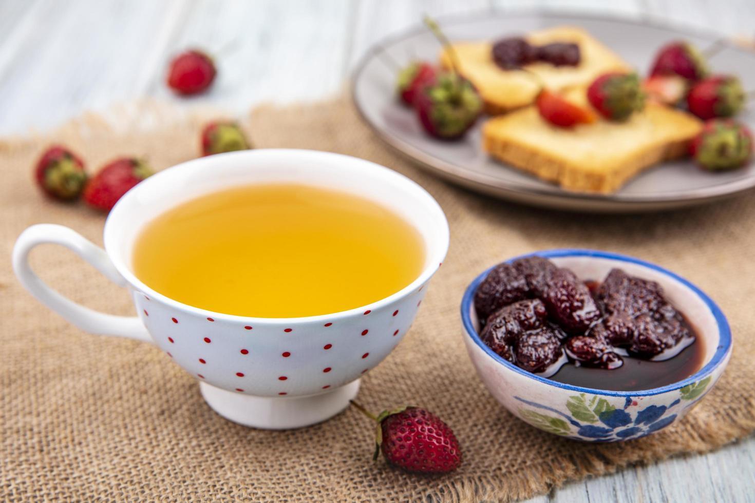 Té y mermelada con tostadas sobre fondo de madera foto