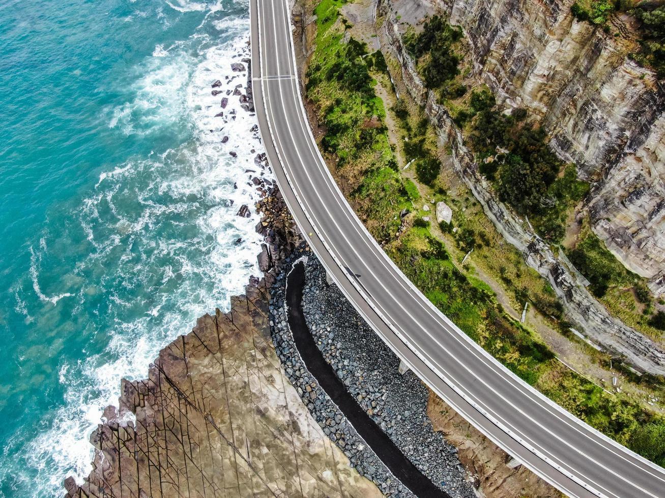 Vista aérea de una carretera cerca de una montaña y el océano. foto