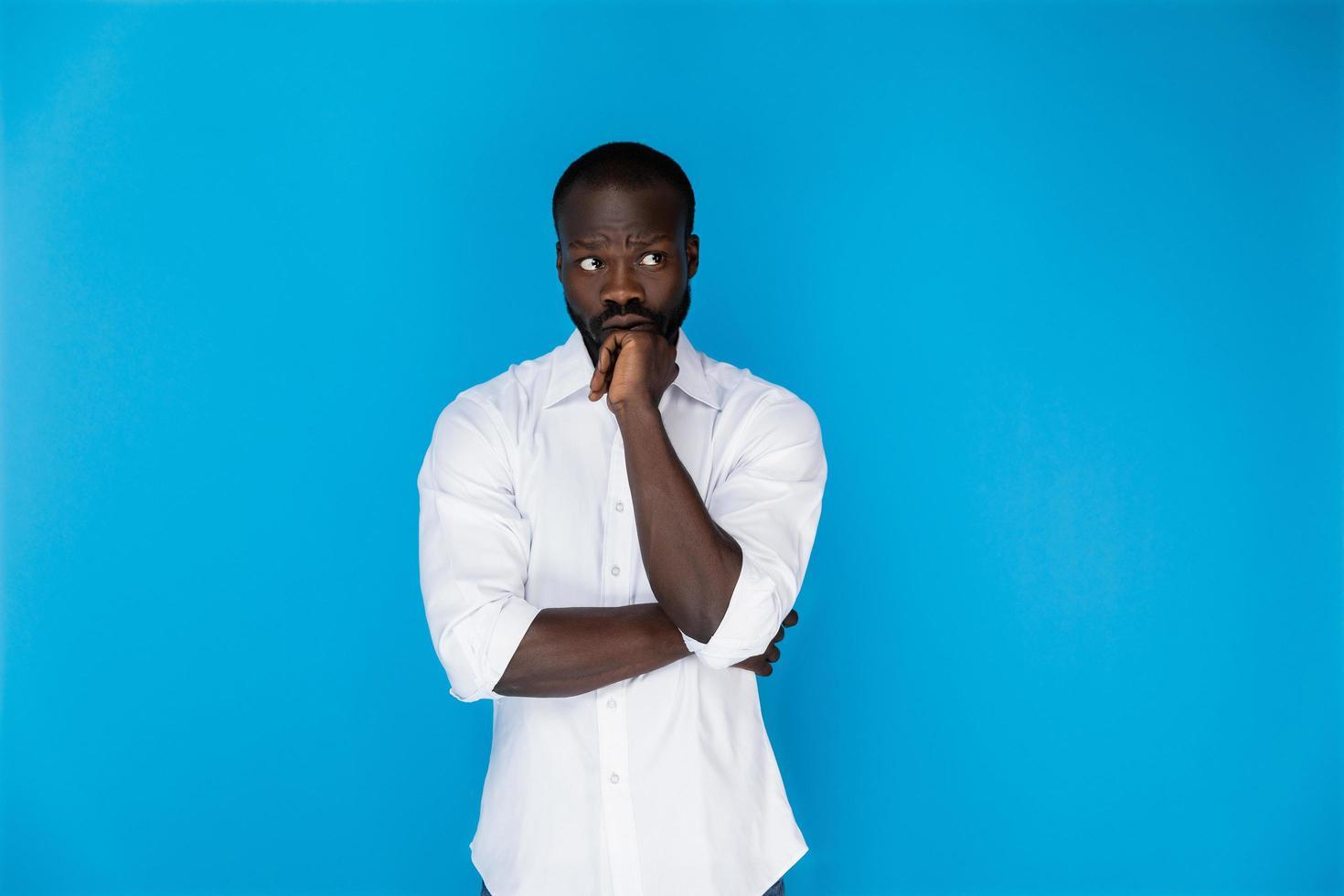 Hombre pensativo en camisa blanca sobre fondo azul. foto