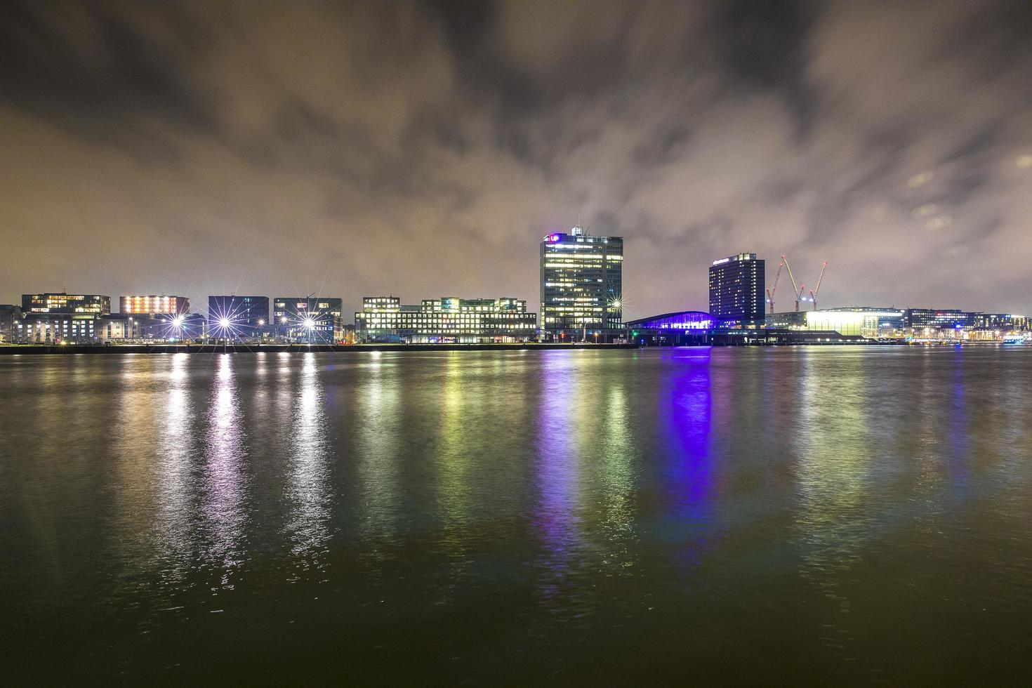 Night view over cityscape river with reflection of modern buildings photo