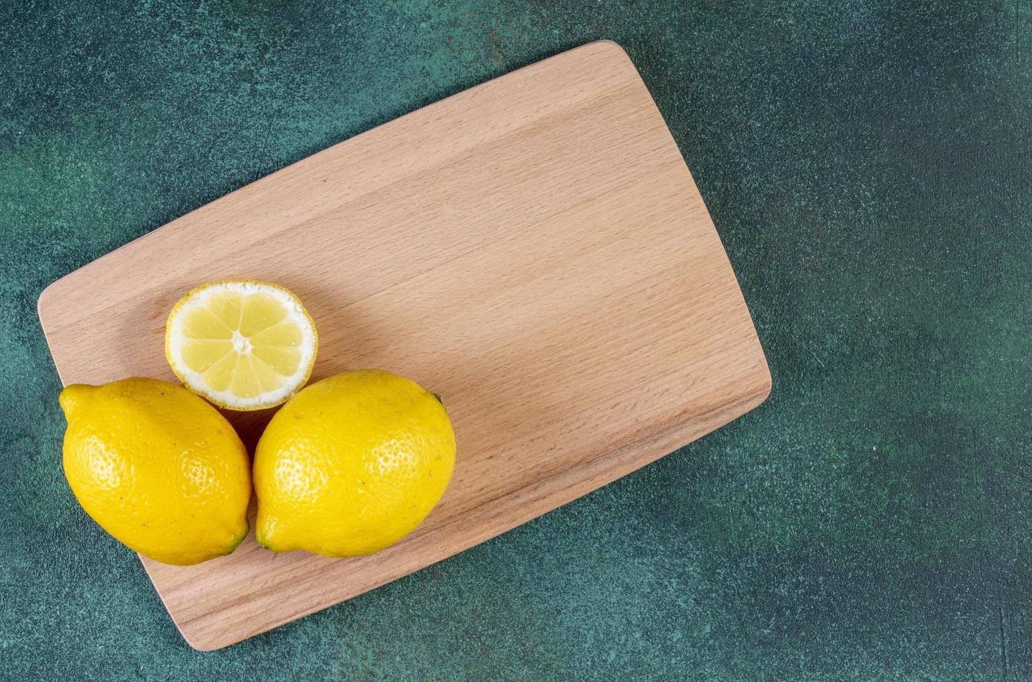 Top view of lemons on blackboard on green background photo