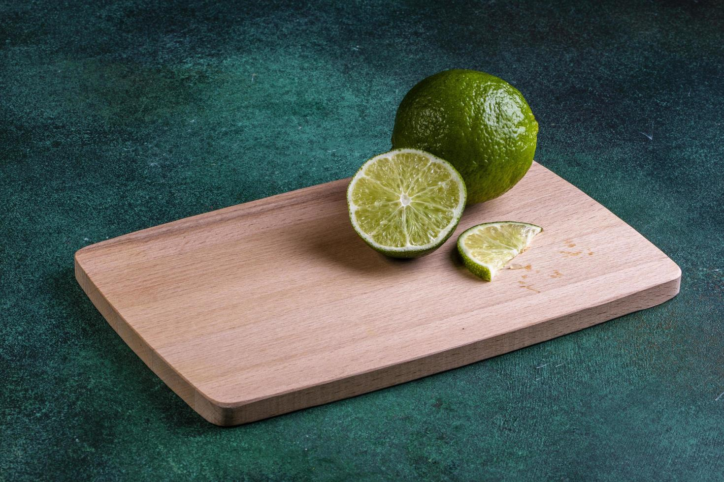 Side view of lime with a slice on the board photo