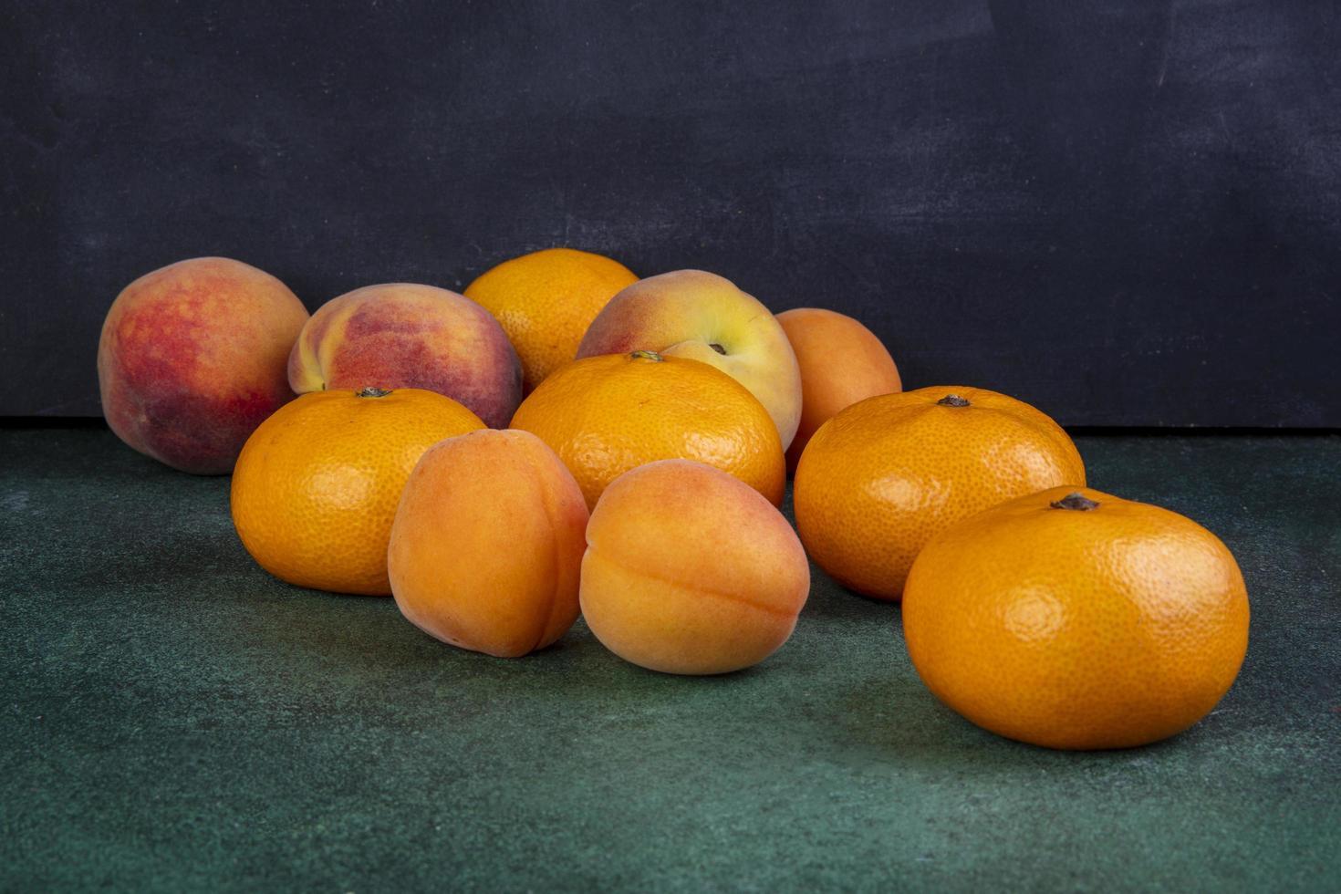 Vista frontal de melocotones con mandarinas y albaricoques. foto