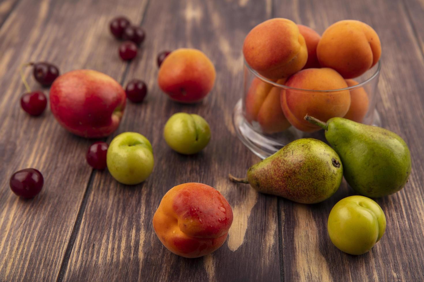 Vista lateral del patrón de frutas como melocotón, cerezas, ciruelas, peras y tarro de albaricoques sobre fondo de madera foto