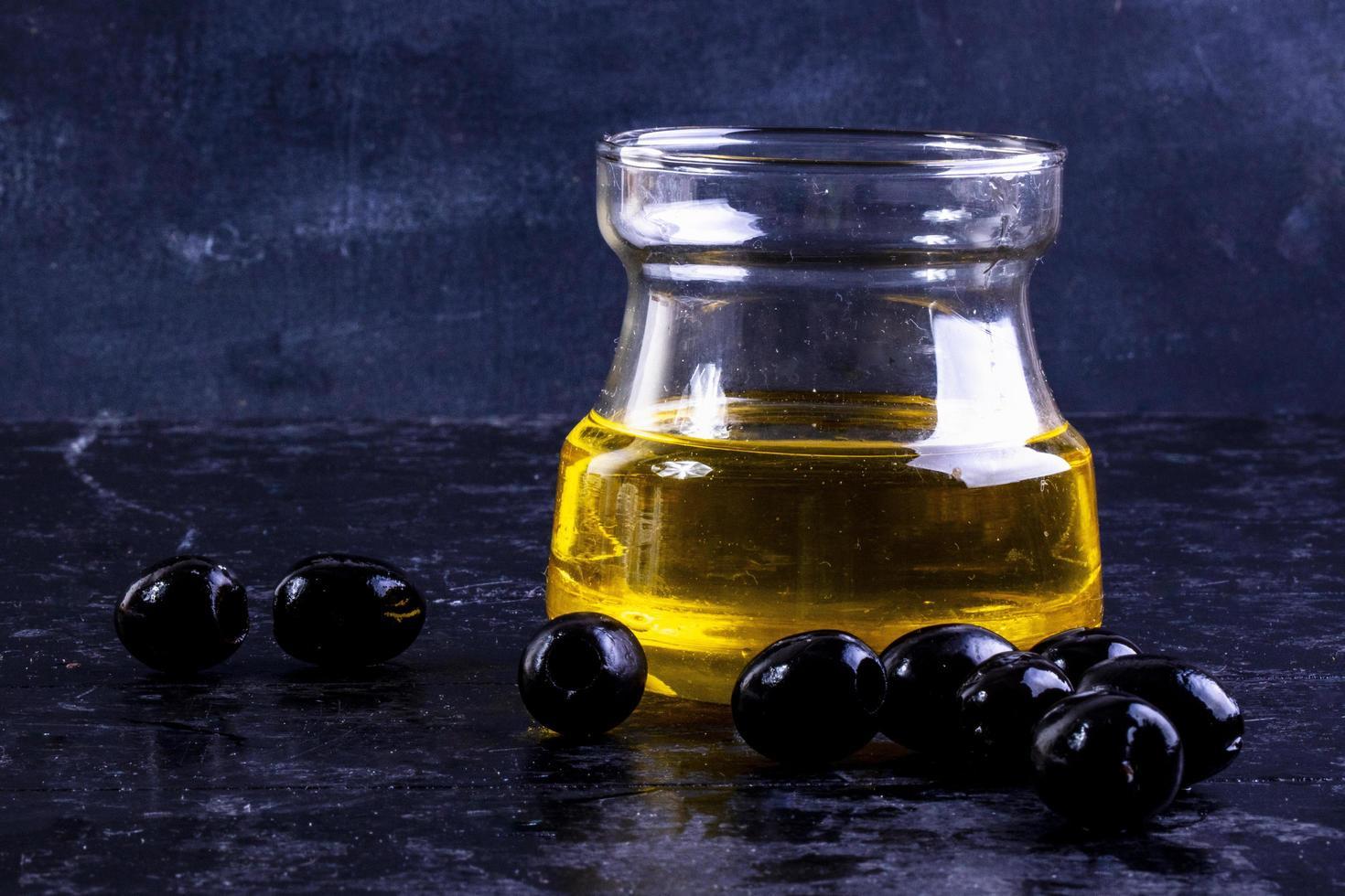 Vista frontal de aceitunas negras con aceite de oliva en un frasco de vidrio sobre un fondo negro foto