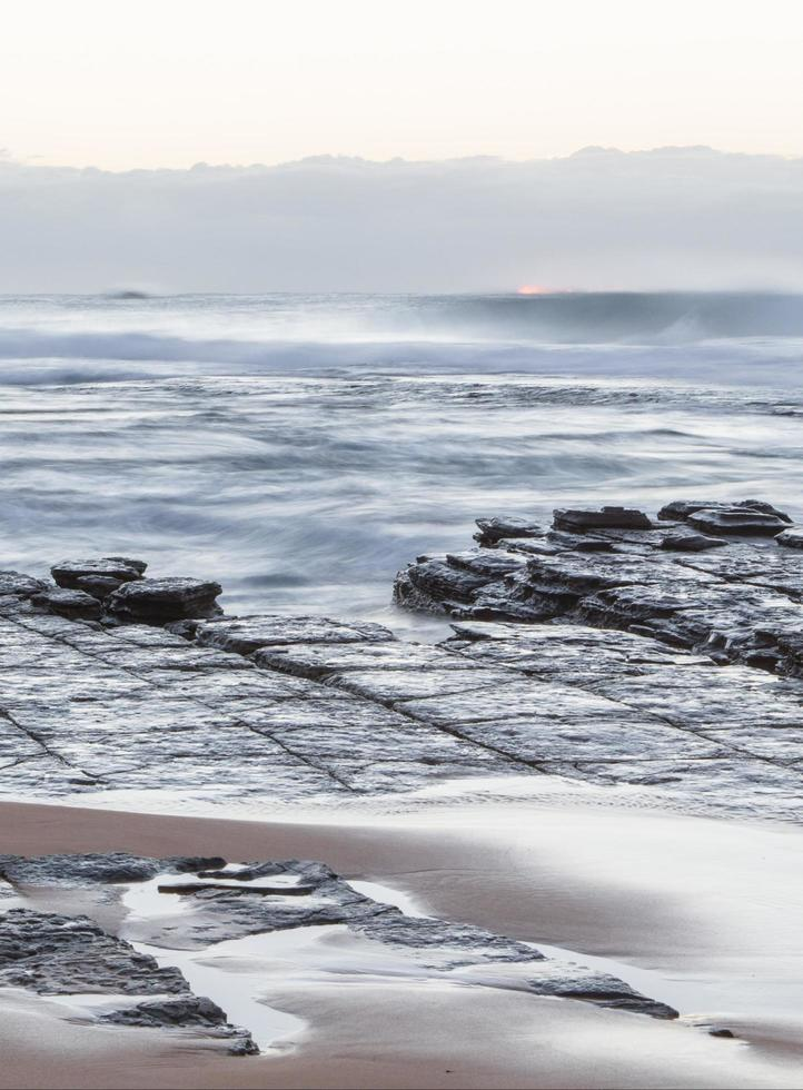Long-exposure of waves on a beach photo