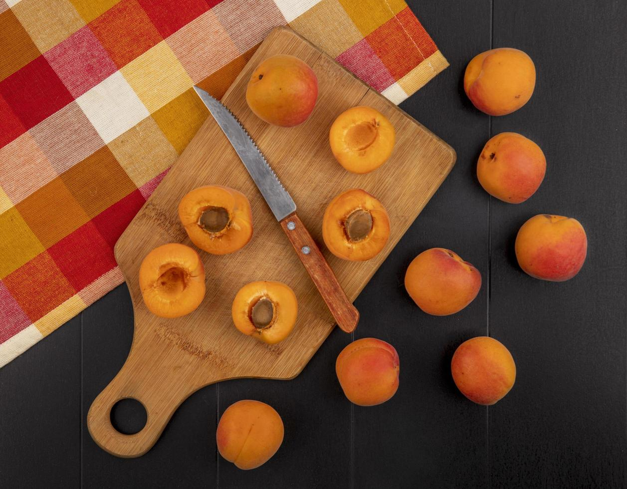Top view of pattern of half cut apricots with knife photo