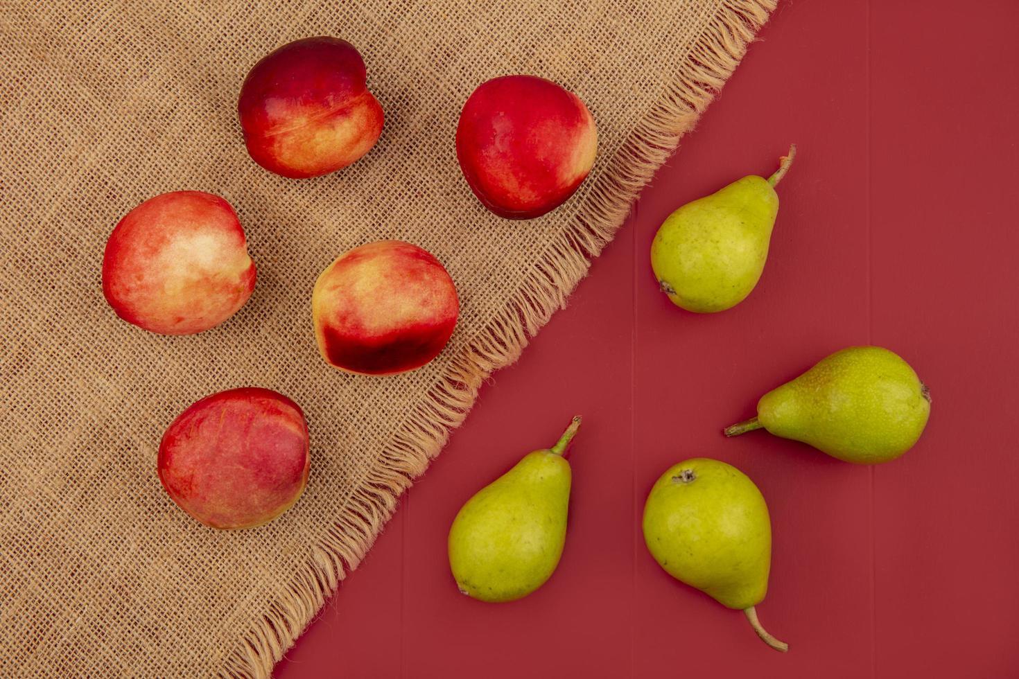 Vista superior de melocotón y peras sobre un fondo rojo. foto