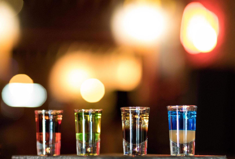 coloridos vasos de chupito en una barra foto