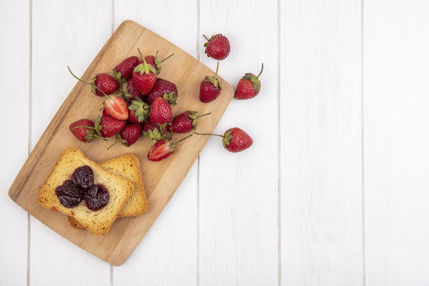 Vista superior de fresas frescas sobre una tabla de madera foto
