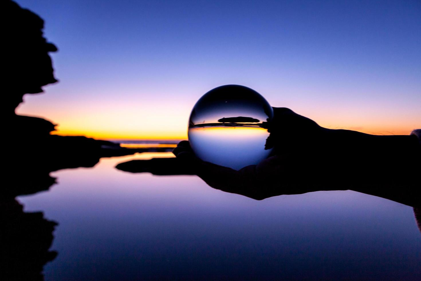 Person holding glass ball at sunset photo