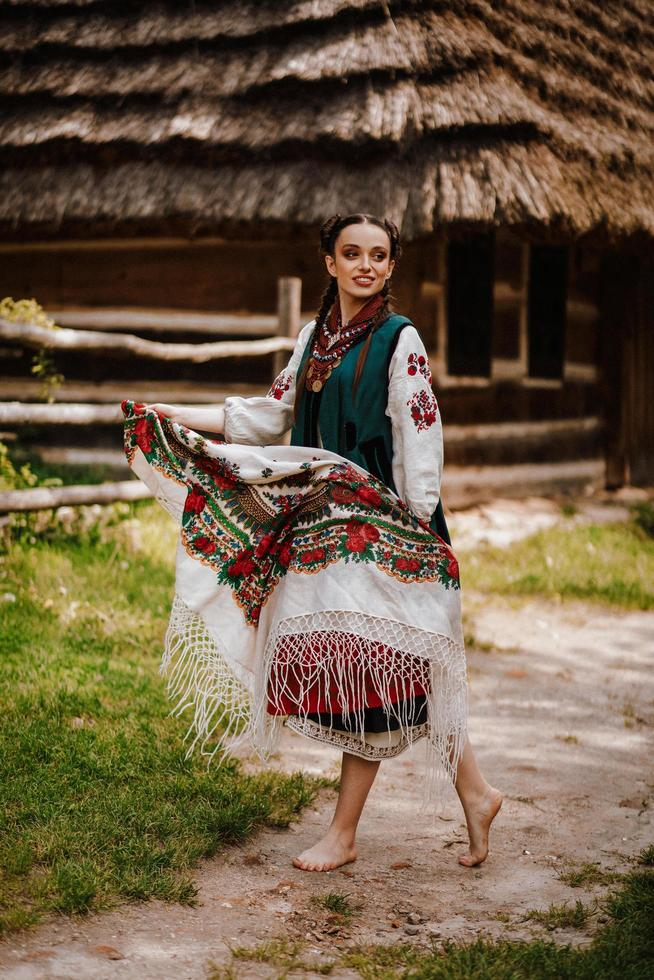 Young girl in a colorful traditional Ukrainian dress dances photo