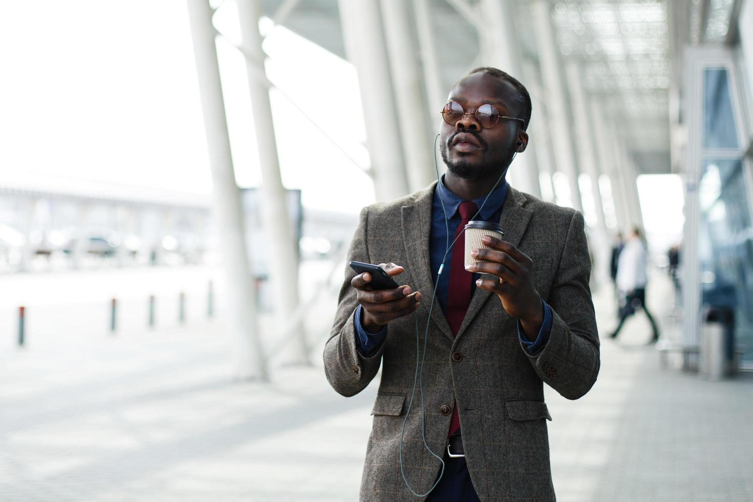 African American business man listens to the music in his smartphone photo