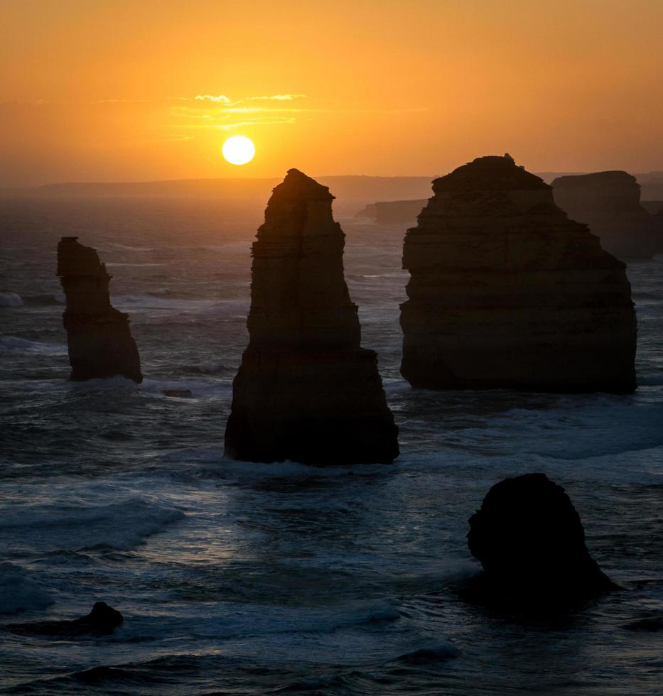 Silhouettes of rocks in the ocean at sunset photo