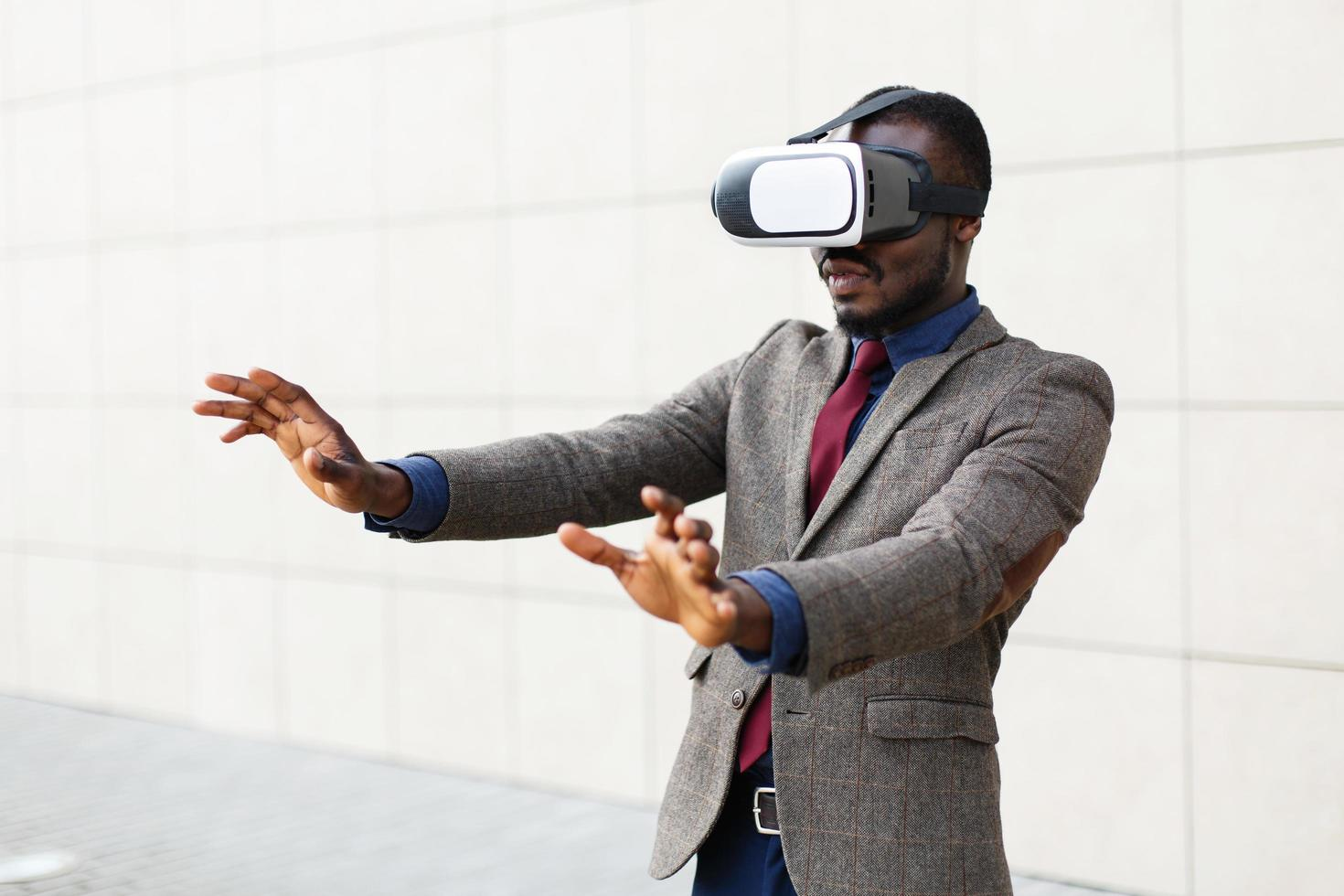 African American business man plays in a VR-glasses standing outside photo