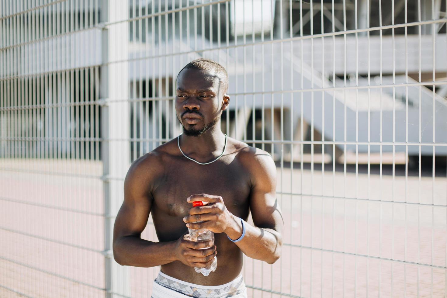 apuesto hombre afroamericano sosteniendo una botella de agua foto