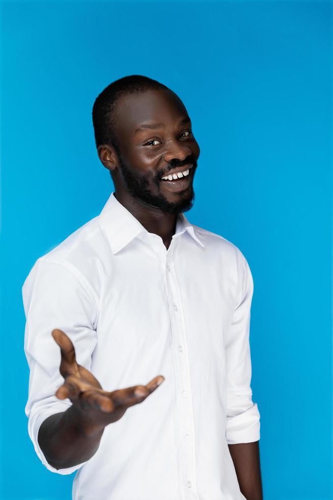 atractivo hombre africano guapo sonríe y da su mano foto