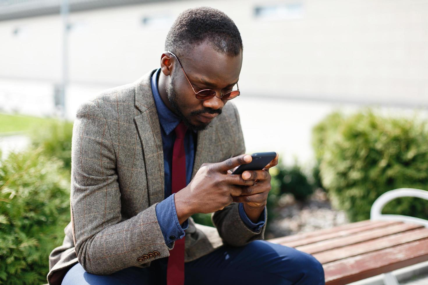 African American business man works in his smartphone sitting on the bench outside photo