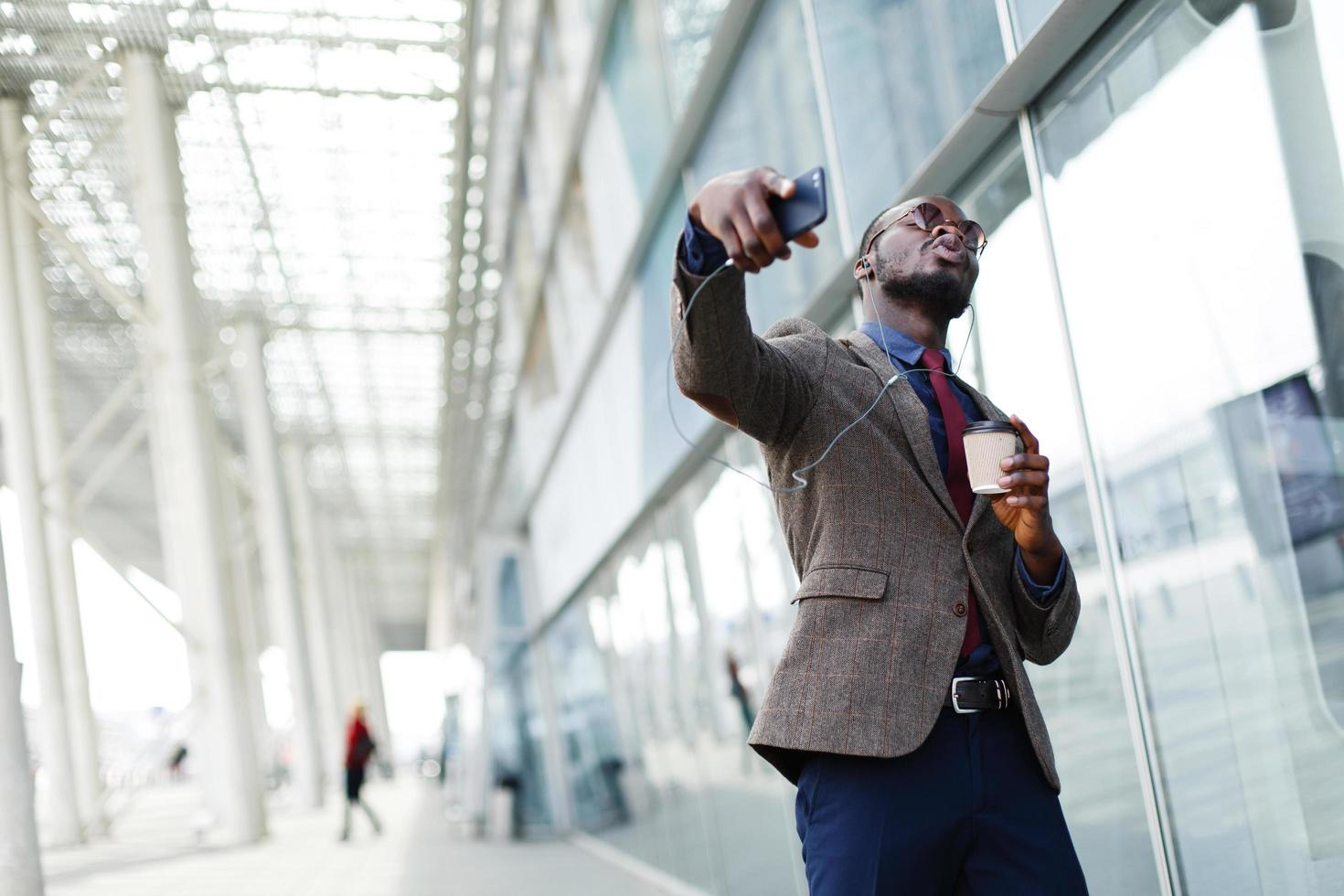 Happy African American business man dances while he listens to the music photo