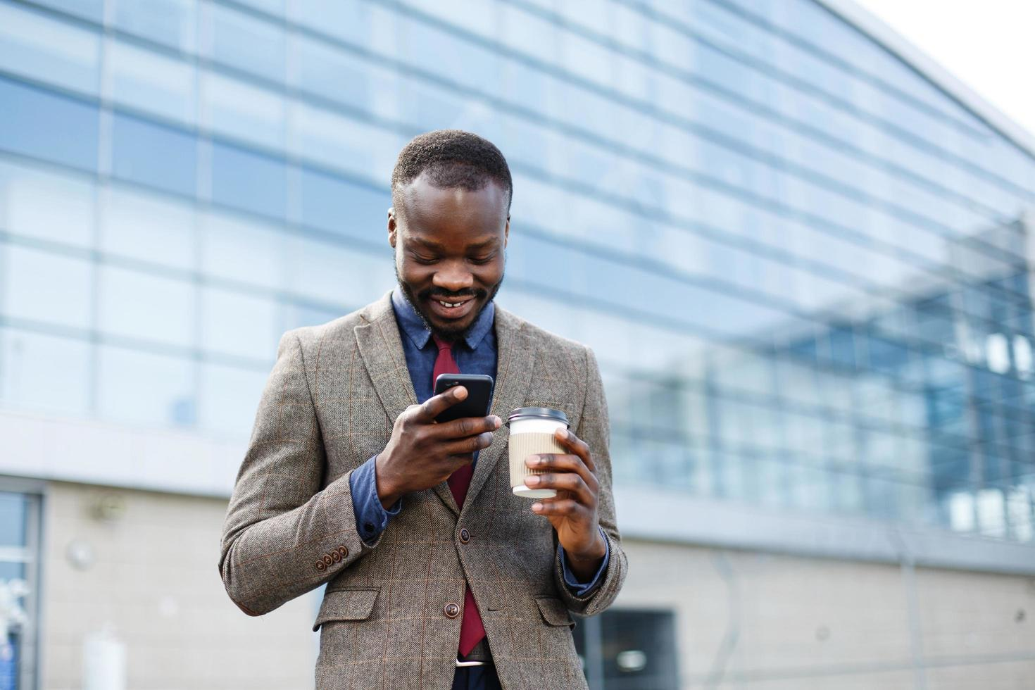 Happy African American man reading something in his smartphone while he stands outside with a cup of coffee photo