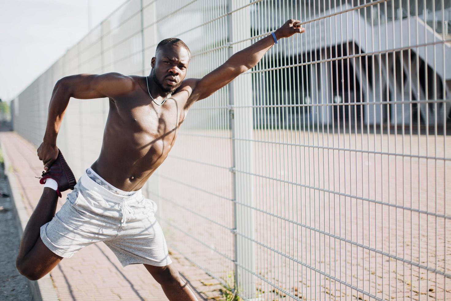 Apuesto hombre afroamericano hace estiramientos antes de un ejercicio exterior foto