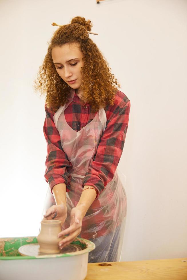 Girl molds a pottery vase photo